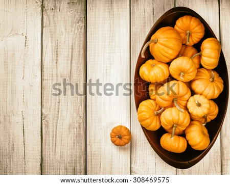 Many Thanksgiving, Colorful Fall Mini Pumpkins in a Wood Bowl on side on Rustic White or brown Painted Board Background with room or space for copy, text, your words  Above view, sepia horizontal - stock photo