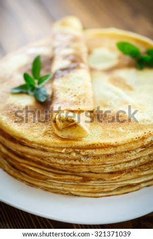 many thin pancakes on a plate on a wooden table