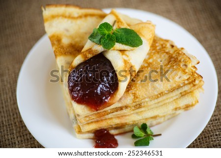 many thin pancakes with jam on the table - stock photo