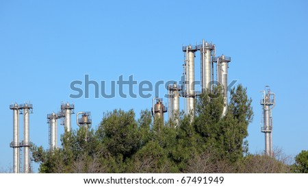 Many towers in an oil refinery over blue sky