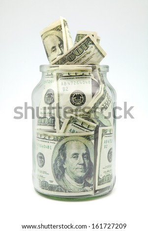 Many 100 US dollars bank notes in a glass jar - stock photo
