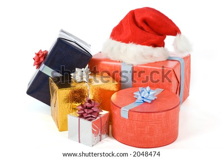 many varicolored gifts and a christmas hat on white - stock photo