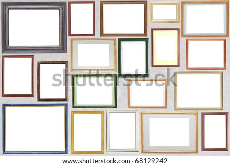 Many various blank wooden frameworks for photos hang on a wall. With clipping patch - stock photo