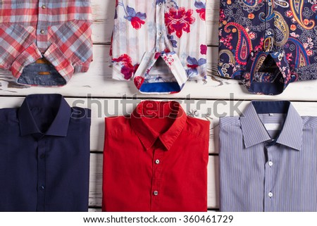 Many various bright modern men's shirts with different colors and prints on old wooden store shelf. - stock photo