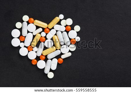 Many various pills and tablets as a heart lie on black background