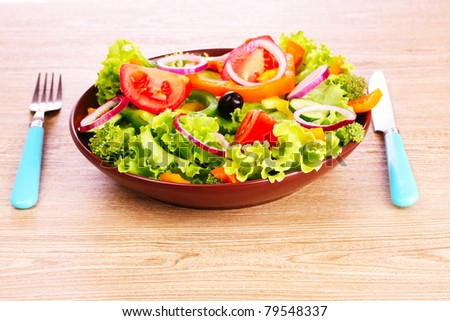 many vegetables on the plate on a wooden background