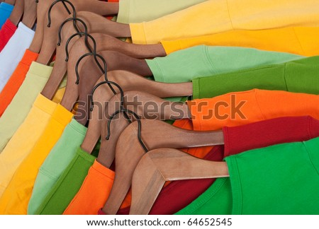 Many vibrant t-shirts of different colors on wooden hangers. - stock photo