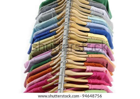 Many vibrant t-shirts of different colors on wooden hangers