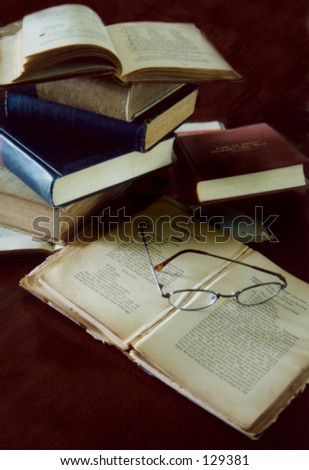 Many vintage books are randomly stacked with glasses laying on an open page. A school or library study theme with lighting from the left. Vertical orientation with small bit of copy space lower left - stock photo