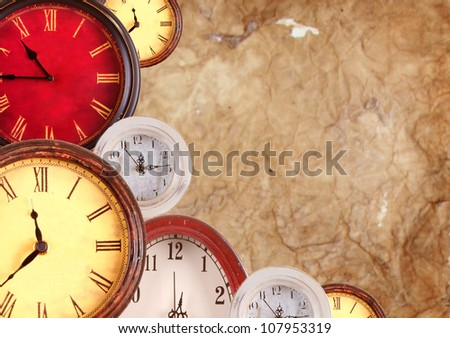 Many vintage clocks on a old paper background