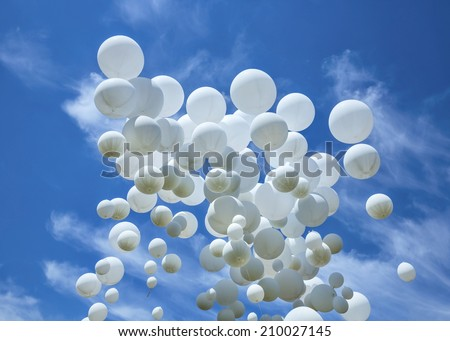 Many white balloons and celebration concept against the blue sky and clouds - stock photo