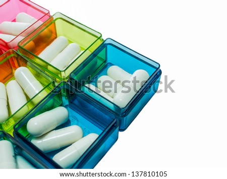 Many white capsule are filled in various color pill box