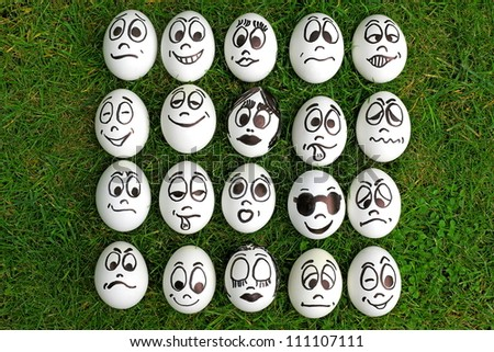 Many white eggs with funny faces - stock photo
