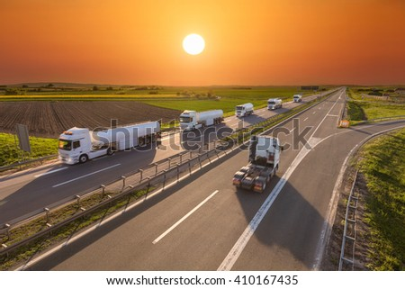 Many white gasoline tanker trucks in line and one without trailer driving towards the sun. Fast blurred motion drive on the freeway at sunset. Freight scene on the motorway near Belgrade, Serbia. - stock photo