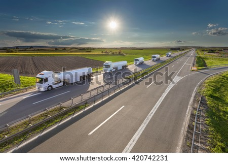 Many white gasoline tanker trucks in line driving towards the sun. Fast gasoline delivery on the freeway at beautiful idyllic day. Freight scene on the motorway near Belgrade, Serbia. - stock photo