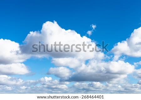 many white puffy clouds in blue spring sky - stock photo