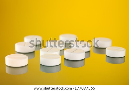 many white tablets on yellow background