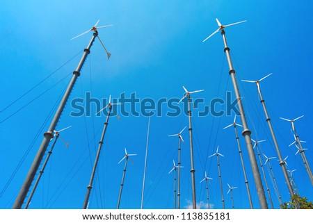 Many wind turbine generating electricity on blue sky - stock photo