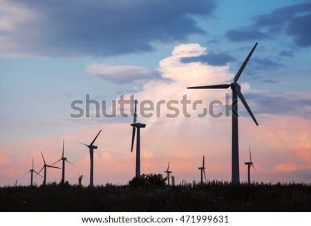 many wind turbines al sunset on summer day