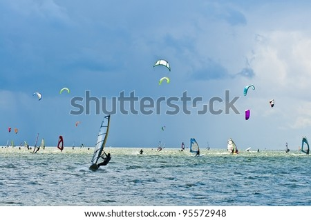 Many windsurfers and kitesurfers - stock photo