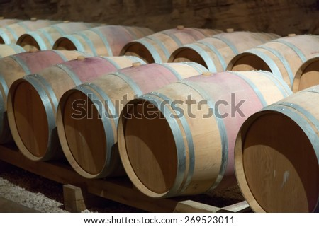 Many wooden barrels in rows at contemporary winemaker factory  - stock photo