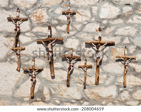 Many wooden crosses on the wall background. - stock photo