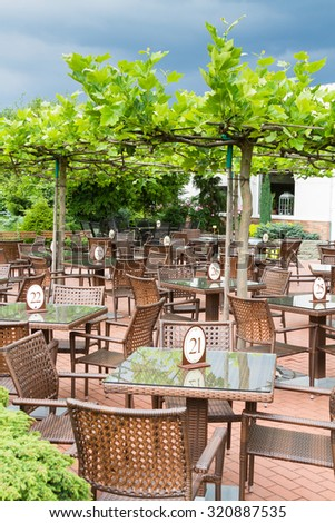 Many wooden teak tables and chairs on brick patio in cafe or restaurant covered by grape vine.  - stock photo