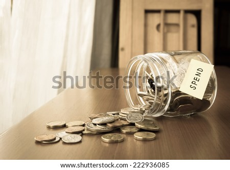 Many world coins spilling out of a money jar, spend word or label on jar - stock photo