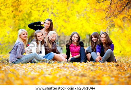 many young girls in the autumn park sitting on the grass - stock photo