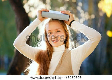 many young girls in the autumn park with books - stock photo