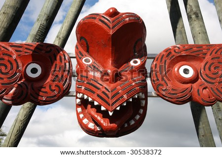 Maori red carving - face carved in the wood. Rotorua, New Zealand. - stock photo