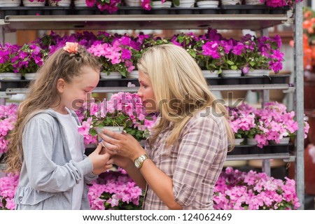 Maothe and daughter smelling plant in garden center - stock photo