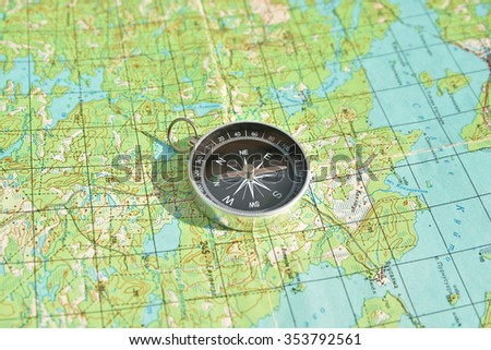 Map and compass. Magnetic compass is located on a topographic map. - stock photo