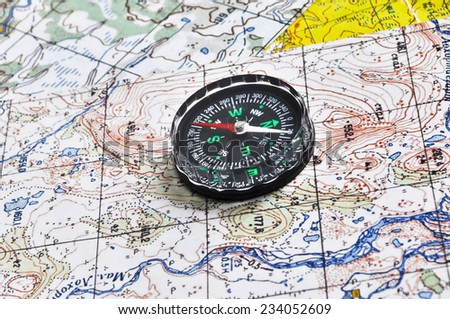 Map and compass. The magnetic compass is located on a topographic map. - stock photo