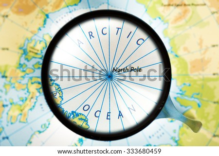Map and magnifying glass. Arctic ocean and North Pole are on the focus.