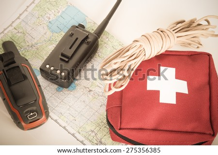 Map, gps navigator, portable radio, rope and first aid kit on a light background. Set lifeguard. Toned. - stock photo