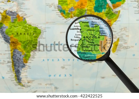 Map of Republic of Angola through magnigying glass - stock photo