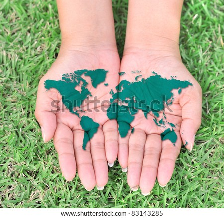 Map of the world in your hands with green grassy background - stock photo