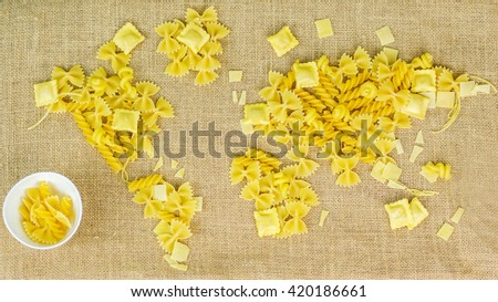map of the world made of raw pasta on brown fabric background with texture with white ceramic bowl full of pasta - stock photo