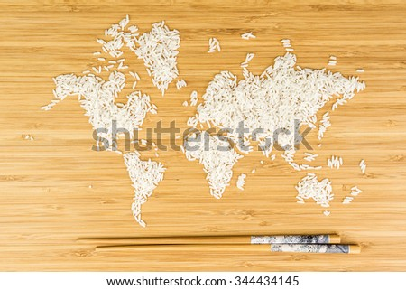 map of the world made of white rice on bamboo wood background with two bamboo sticks - stock photo