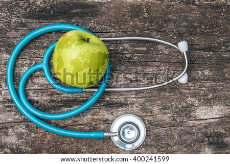 Map on healthy fruit food green fresh organic natural nutrient apple w/ doctor's stethoscope heart shape grunge old aged wood background: World health day WHD April 7 symbolic conceptual design idea  - stock photo