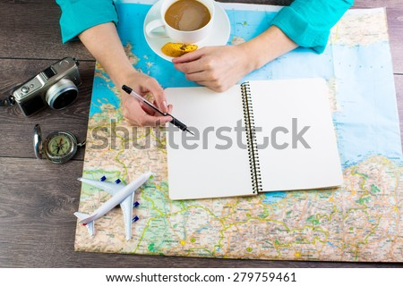 Map traveler. Woman bent over the map in search of a best route for the next vacation time to travel. Empty space in a notebook for blog entries, you can place your text. Top view - stock photo