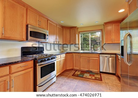 Maple kitchen cabinetry, granite counter top, steel appliances and tile floor. Kitchen room interior. Northwest, USA