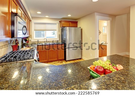 Maple kitchen cabinets with steel appliances and granite tops. - stock photo