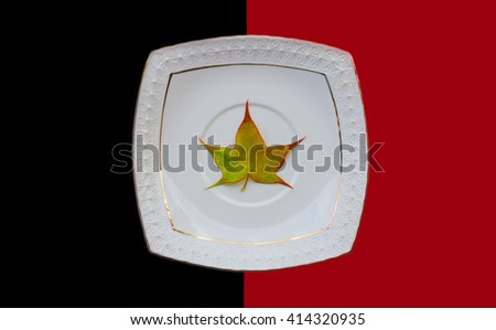 maple leaf in a white ceramic saucer on a red black background - stock photo
