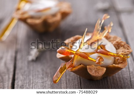 Maple mousse in almond basket with caramel decoration - stock photo