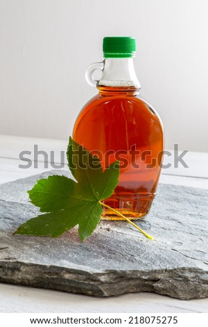 Maple syrup in a bottle with maple leaf. - stock photo