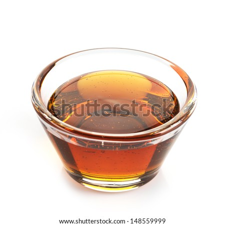 Maple syrup in a bowl on white background - stock photo