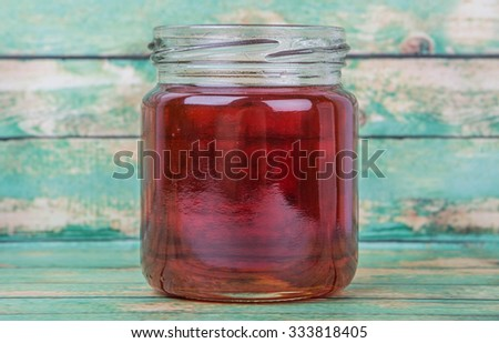 Maple syrup in a mason jar over wooden background