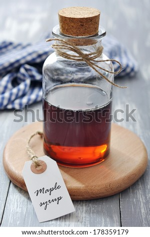 Maple syrup in glass bottle on a wooden background - stock photo